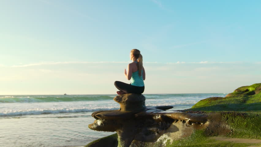 Happy young woman practicing yoga on the beach at sunset. Healthy active lifestyle concept. Slow Motion