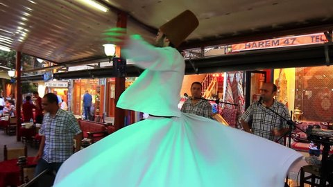 ISTANBUL - JUL 15, 2013: Semazen dervish whirling, his arms are open. His right arm is directed to the sky, ready to receive Gods beneficence and his left hand is turned toward the earth