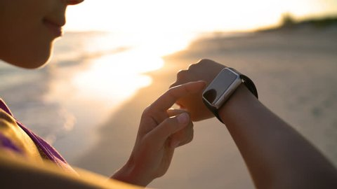Woman touching smartwatch on beach during sunset. Closeup of female using smart watch app outdoors.