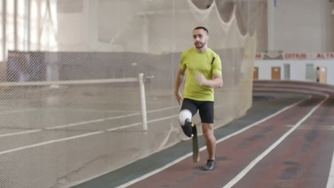 Paralympic athlete with prosthetic leg running on track in practice, slow motion