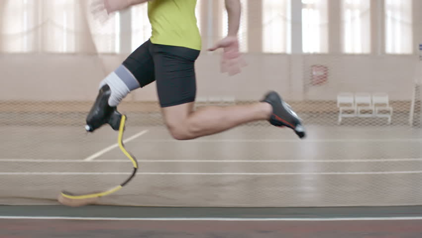 Tracking shot of Paralympic athlete with prosthetic leg running on track in slow motion | Shutterstock HD Video #15805765