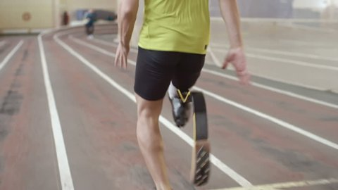 Follow shot of amputee runner with prosthetic leg running on track at indoor stadium in slow motion