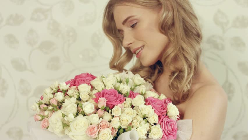 Charming blonde with wavy hair posing with a large bouquet of roses #15809707