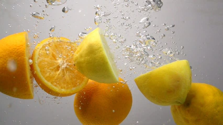 Lemon and orange drops into water in slow motion