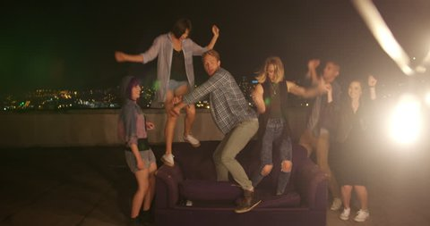 Multi-ethnic group of teenager friends dancing with raised arms and laughing during a night rooftop party