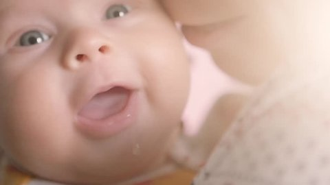 Close up of baby's face while it smiles and laughs. Happy child in mother's hands. Motherhood concept.