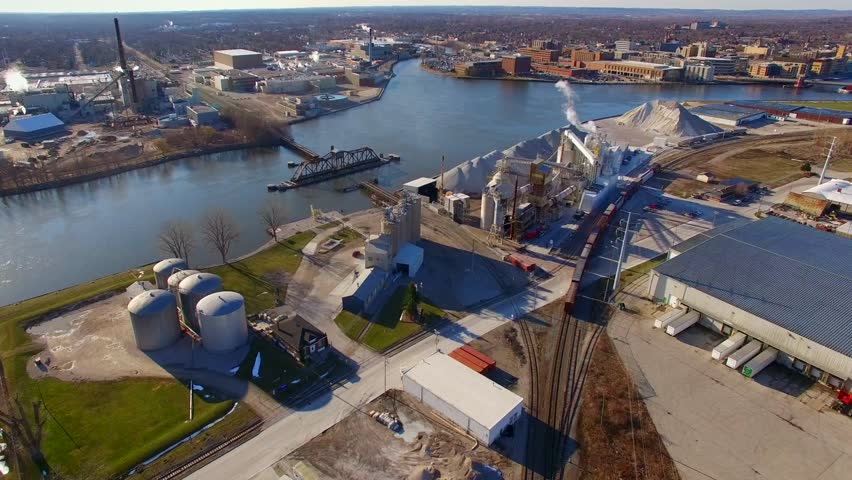 Aerial flyover of industrial zone with scenic railroad bridge, Green Bay, Wisconsin. The downtown area is also visible.   Shutterstock HD Video #15863167