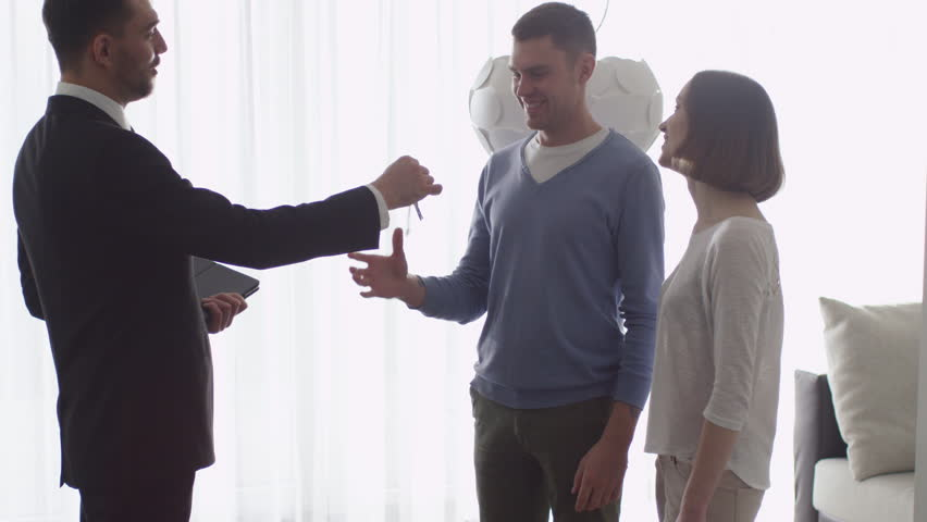 Real-estate Agent Shows New Apartments to Couple and Giving the Keys to a Man.  Shot on RED Cinema Camera. | Shutterstock HD Video #15904204
