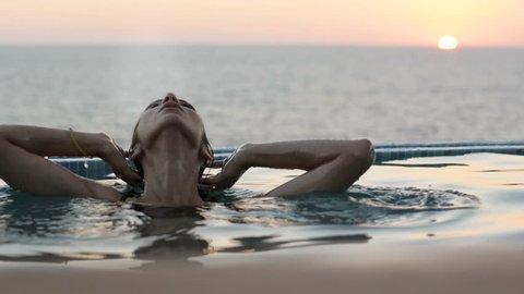 Luxury resort woman relaxing in infinity pool