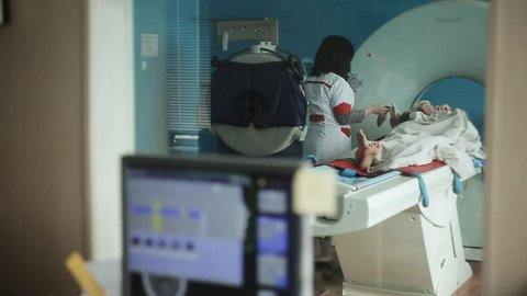 Mid adult nurse preparing patient for CT scan test in hospital