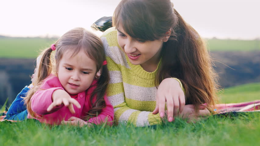 Mum and daughter lie on the grass, talking | Shutterstock HD Video #15924997