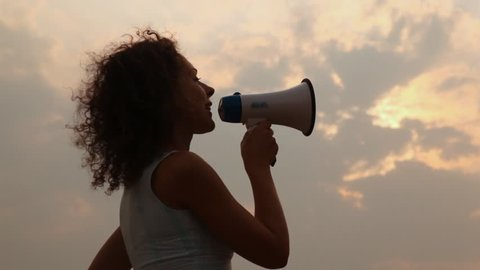 woman stands and tells something in megaphone lifts it upwards