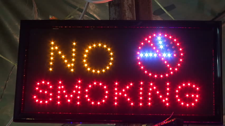 No Smoking Sign. A colorful electronic no smoking sign with flashing LED lights. Pan down to a similar ladies and Gents toilet sign.