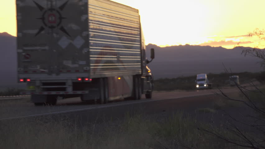 4K CLOSE UP: Cars and big freight transporting semi trucks driving on busy highway after the sunset in summer. Traffic speeding on busy freeway in the evening.