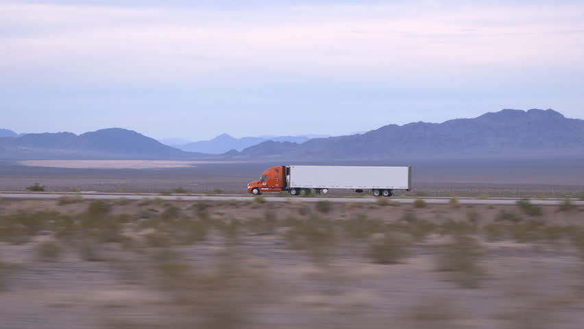 4K CLOSE UP: Freight semi truck driving and transporting cargo container on empty highway, delivering goods
