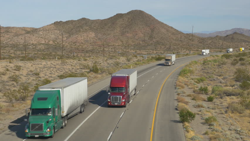 4K AERIAL SLOW MOTION CLOSE UP: Cars and trucks driving on busy highway through the desert. Freight semi trucks transporting goods, personal cars on a road trip, people traveling in sunny summer