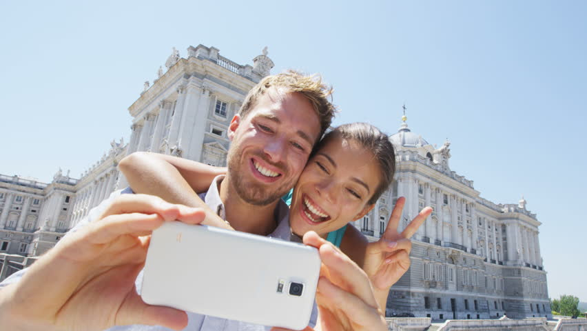 Couple taking selfie photo on smartphone in Madrid. Romantic man and woman in love using smart phone to take self-portrait photograph on travel in Madrid, Spain by Palacio Real de Madrid.