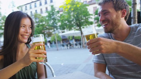 Couple eating tapas drinking beer in Madrid, Spain. Romantic man and woman enjoying local traditional food on square in Madrid. Asian woman and Caucasian man dating. Focus on beer and food.