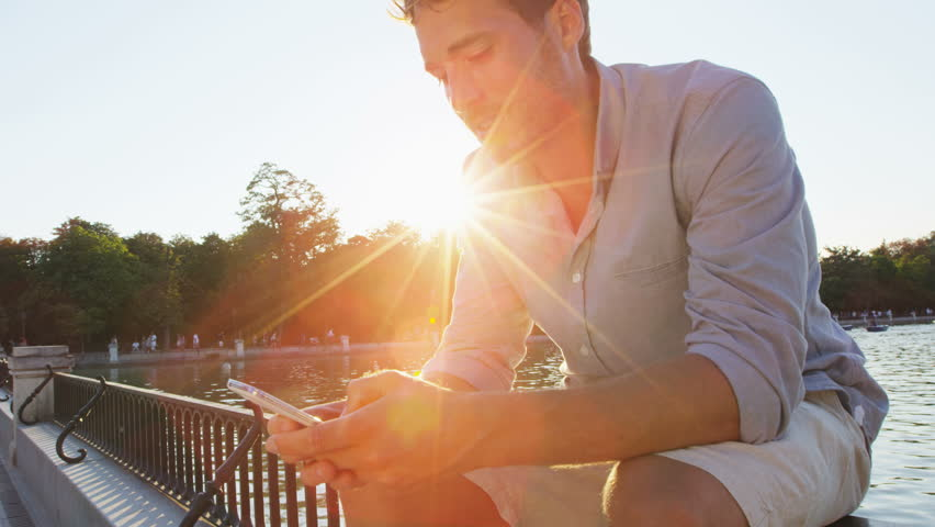 Man sms texting using app on smart phone at night in city park. Handsome young business man using smartphone smiling wearing shirt outdoors. Urban male professional in his 20 at sunset.