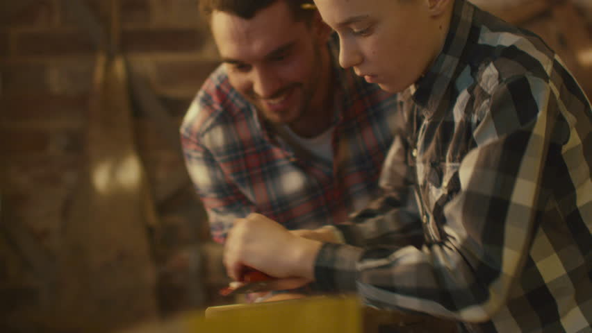 Father and son are woodworking in a garage at home. Shot on RED Cinema Camera in 4K (UHD).