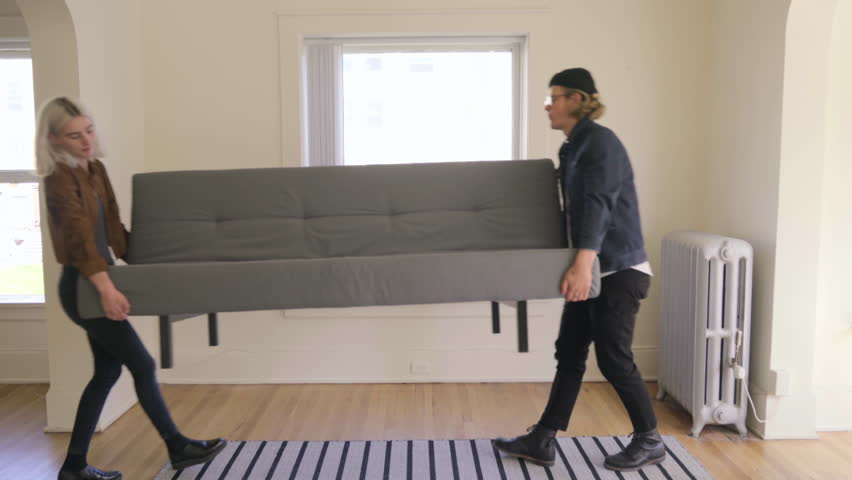 Captivating Young Trendy Couple Move A Couch Into New Apartment, They Set It Down,  Adjust