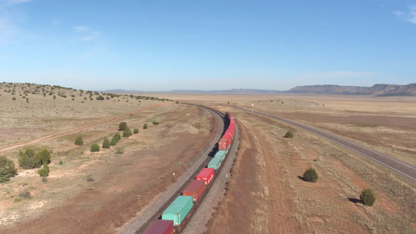 SELIGMAN ARIZONA USA, OCTOBER 20th 2015: AERIAL: Long container freight train with many cargo wagons transporting goods through the vast desert landscape across the country