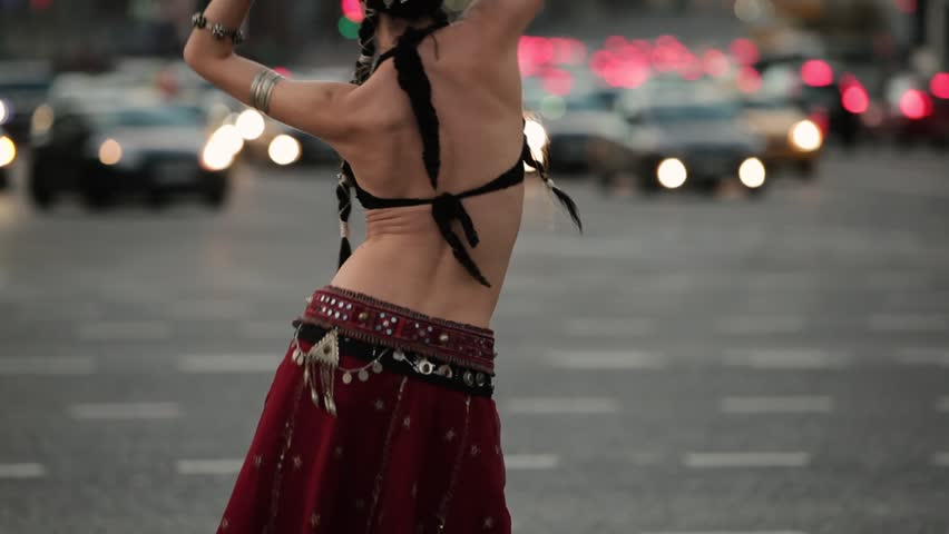 Young girl in etnic costume dancing tribal on the city. In the background a city road with lot of cars. | Shutterstock HD Video #16004077