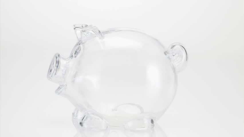 July 25, 2011: Transparent piggy bank filling up with coins on white background
