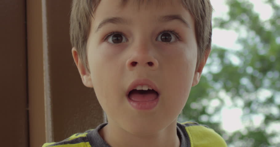 RED 2K slow motion shot of a shocked boy. Camera pans around him as he slowly turns.