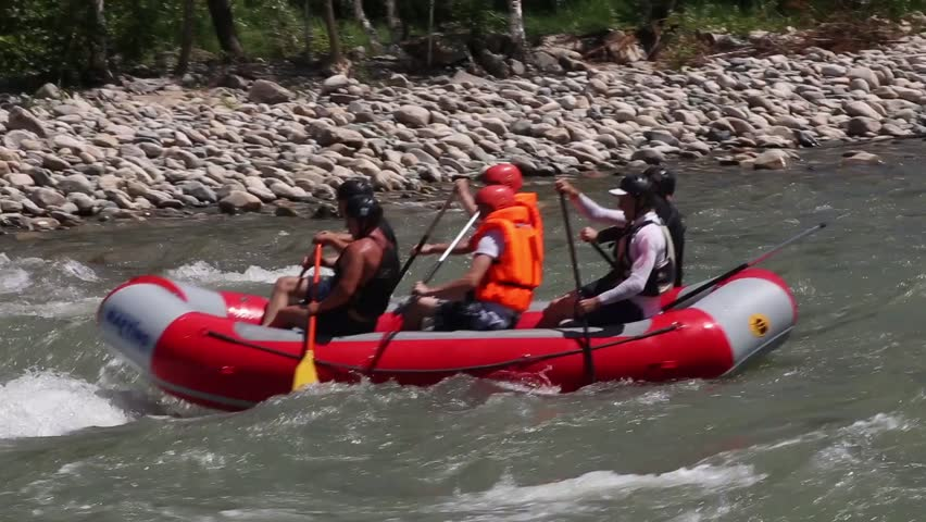 Group of six people white water rafting