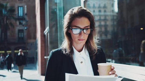 Close-up of young attractive businesswoman wearing glasses and drinking coffee to take away while working with documents outdoors, looking serious and concentrated, slow motion