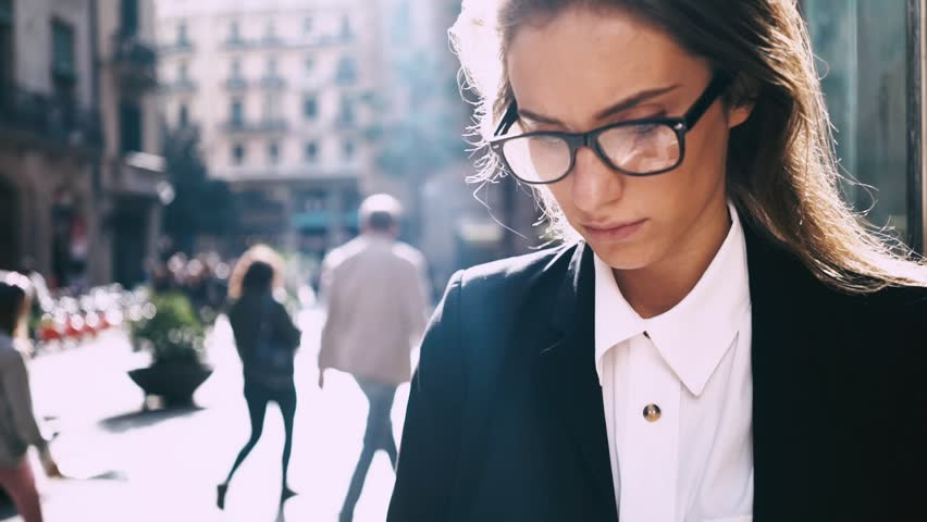 Close-up of young professional businesswoman using smartphone and drinking coffee to go outdoors, sunlight, slow motion