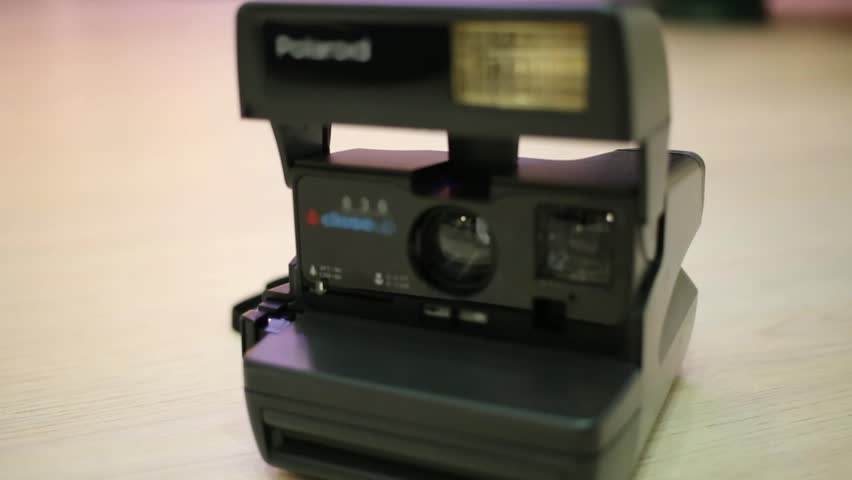 A old fashioned camera polaroid is standing on the table.