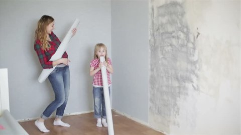 Cheerful girls are dancing and singing near the wall with rolls of wallpaper in their hands. Happy funny family is fooling around. Pregnant woman and her daughter are doing repair in the room.