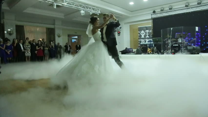 Beautiful young newlyweds dancing their first dance shrouded by white fume. Wedding celebration in the restaurant