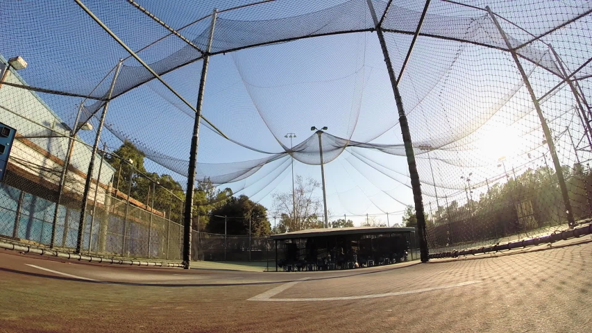 A baseball player practicing at the batting cages. - Model Released - filmed at 59.94 fps #16071367
