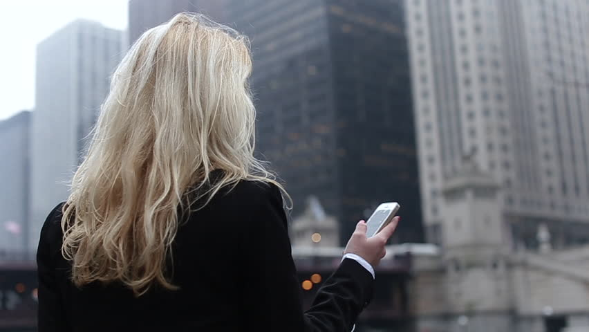 Attractive Blonde Business Woman Using Smartphone Commuter in City, Pretty Young Business Woman Talking by Phone Against Complex of Modern Office Buildings.a Beautiful Girl With a Black Bag in Hand,a