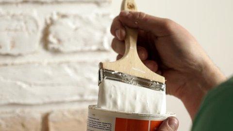 Renovation: man painting a wall, enjoying the work. Slow motion. Close up