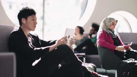 Asian Male watching digital tablet in airport waiting lounge