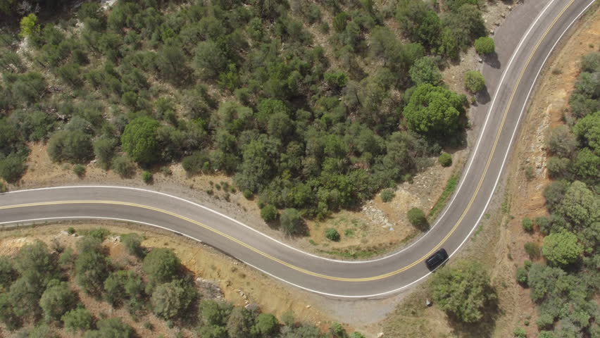 AERIAL: Black SUV jeep car driving along the winding mountain pass road through the forest. People traveling, road trip on curvy road through beautiful countryside scenery in sunny summer