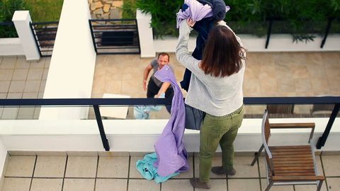 Couple fighting, woman throwing out clothes from terrace