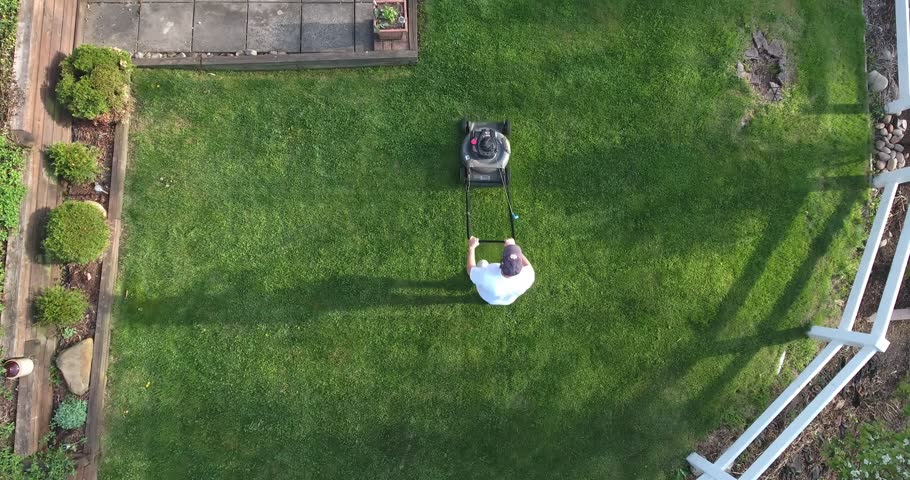 An aerial view of a man mowing the lawn.