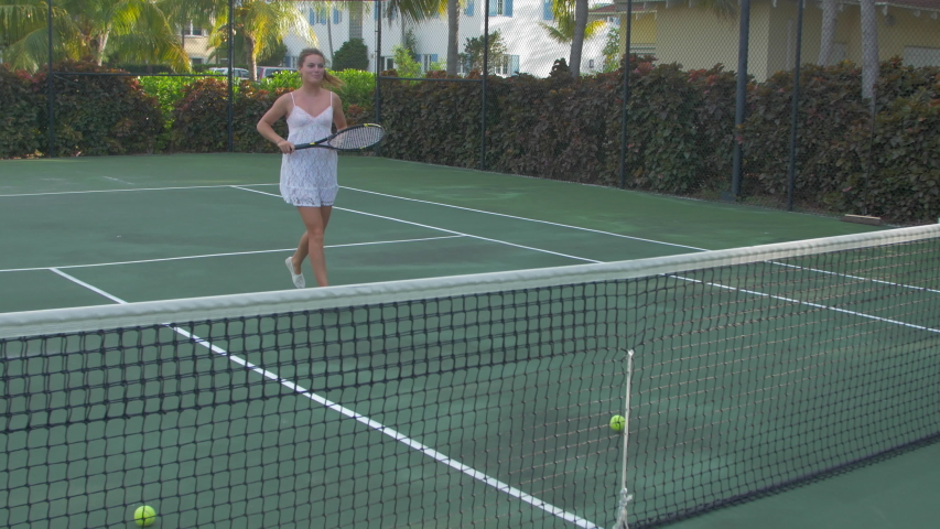 A Young Woman Playing Tennis With Her Boyfriend While On Vacation