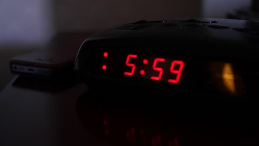 A digital alarm clock turns on at six o'clock and a man turns it off | Shutterstock HD Video #16225447