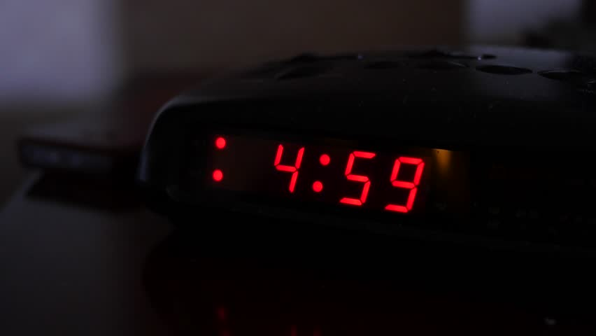 A man turns off the alarm when a digital alarm clock turns to five o'clock | Shutterstock HD Video #16225459