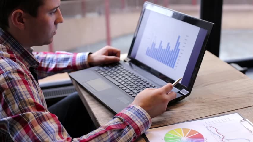 A man exploring on a laptop, and the statistics printed on paper