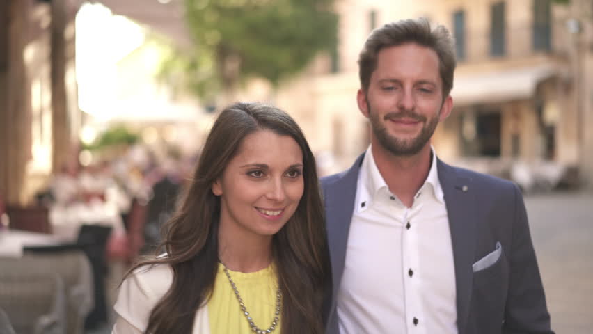 4k footage, young rich hipster couple walking through old town at late afternoon, ending in bright sunshine