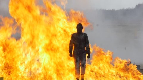Stunt girl in a fiery explosion. Slow motion. Beautiful girl stunt runs across the field through the explosions and fire.
