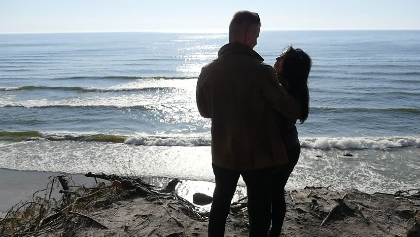 Man kissing woman silhouette against sun - cliff with sea view slow motion 2