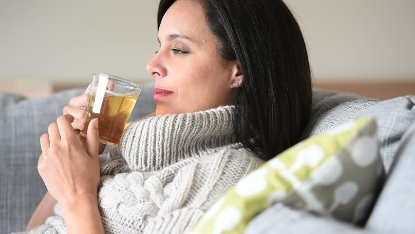 A woman drinking a sambong tea